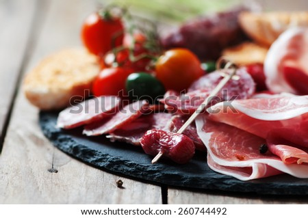 Antipasto with ham, olive and tomato on the wooden table, selective focus - stock photo