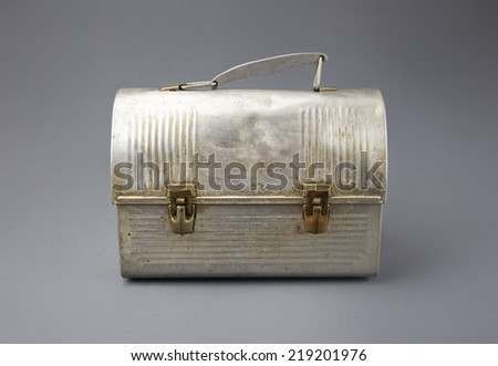 Antique aluminum lunch box against gray background.  - stock photo