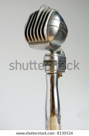 Antique appearing microphone on white field - stock photo