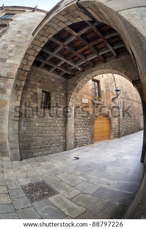 Antique architecture elements as masonry walls, stone sidewalks and arches are frequently found  on the narrow but charming streets of Barcelona's gothic quarter. This one is Montjuic Bisbe street. - stock photo