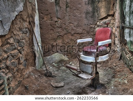 Antique Barber Chair in a Cell in Eastern State Penitentiary in Philadelphia, Pennsylvania - stock photo