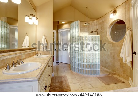 Antique bathroom design with glass shower and tile wall. Has large mirror on the wall and white cabinets with two sinks.