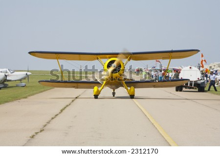 Antique biplane taxing on runway - stock photo