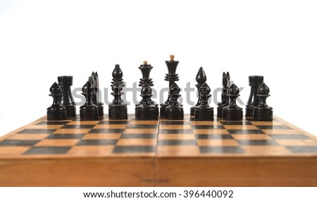 Antique black chess figures on the chessboard (isolated on white, with copy space for your text), shallow DOF with selective focus on the figures - stock photo