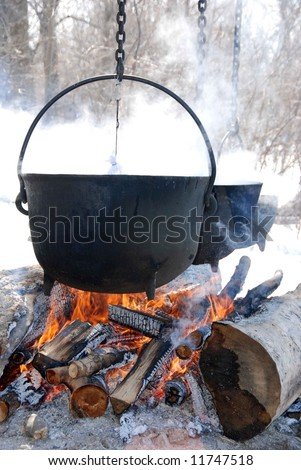 Antique black kettles on an open fire - stock photo