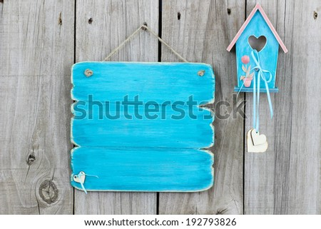 Antique blank teal blue sign with blue and pink birdhouse with wood hearts and flowers hanging on wooden fence - stock photo