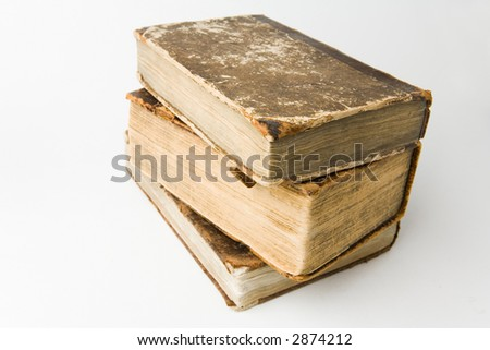 Antique books piled on a white background - stock photo