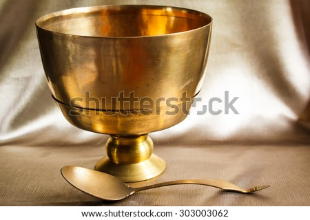 Antique brass bowl and ladle, still life art photography on vintage, thai style.