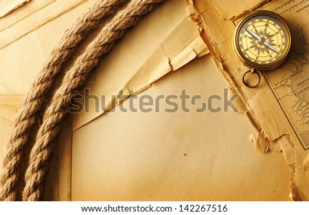 Antique brass compass and rope over old map
