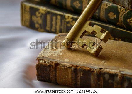 Antique brass key with antique books, artistic vintage still life, concept of the key of knowledge in reading - stock photo