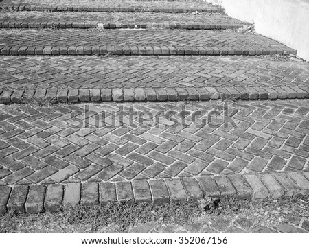 Antique brick steps with diagonal design and point of focus on the center of the image, in tones of black, white, and gray/grey. - stock photo