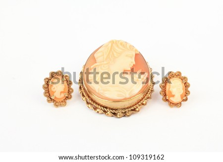 Antique cameo brooch set in gold with matching earrings against neutral background. - stock photo