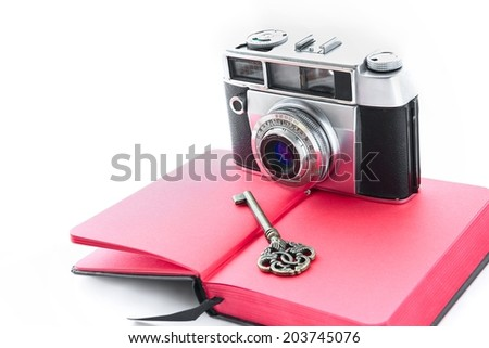 Antique camera on red notebook on white background. - stock photo