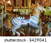 Antique Carousel with colorful horses - stock photo