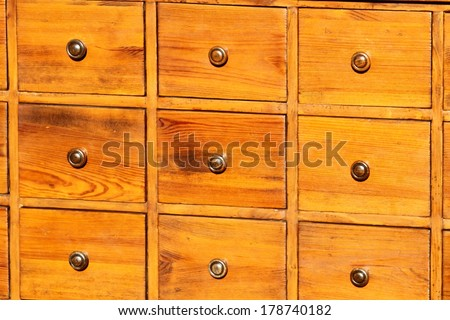 antique chest of drawers in solid wood with brass knobs on sale in antiques shop - stock photo