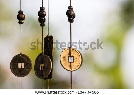 Antique Chinese coins hanged outside the house as wind chimes  for protection and good luck - stock photo