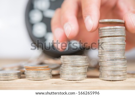 Antique clock and Hand stacking up Thai coins - stock photo