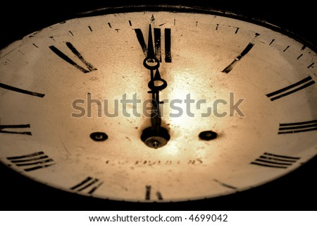 Antique clock face with the hands at 12 o'clock, sepia toned image. - stock photo