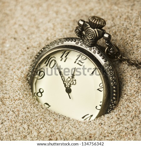antique clock in the sand - stock photo
