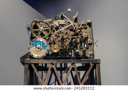 Antique clock mechanism over grey background. - stock photo