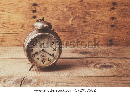 Antique clock over an old vintage table - selective focus, copy space - stock photo
