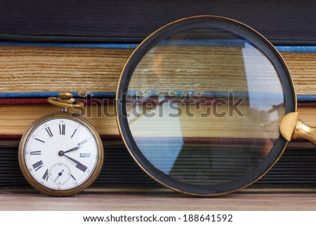 antique clock with finding glass  on vintage books background - stock photo