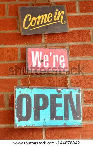 Antique Come in We're Open Sign Hanging on a Brick Wall - stock photo
