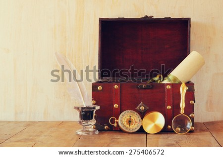 antique compass, inlwell and old wooden chest  on wooden table - stock photo