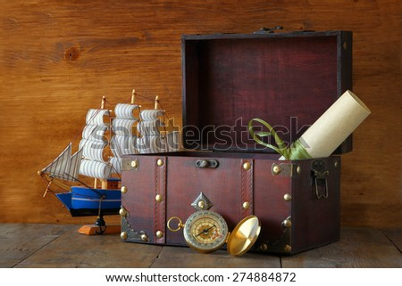 antique compass, manuscript, old vintage chest on wooden table - stock photo