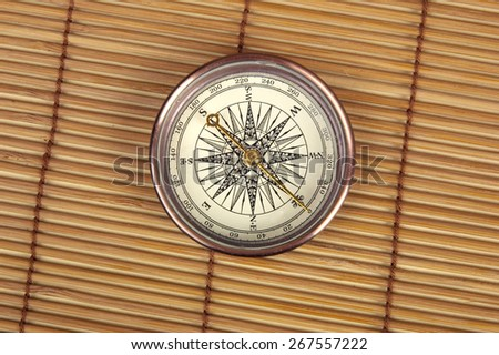 Antique compass on a light wooden background. - stock photo