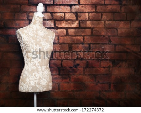 Antique dress form with vintage look against brick background - stock photo