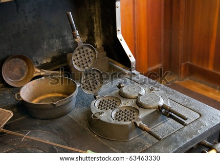 Antique farmhouse stove in cast iron with old waffle of pancake maker