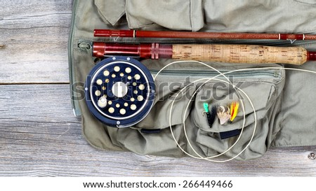 Antique fly fishing reel and rod with vest and flies on rustic wood. Layout in horizontal format. - stock photo