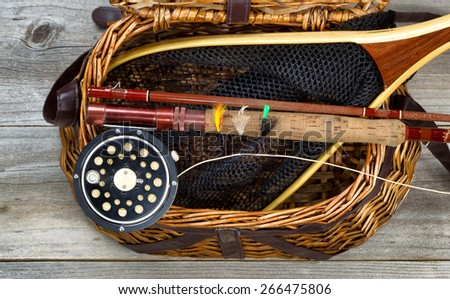 Antique fly fishing reel, rod, flies, and net on top of open creel with rustic wood underneath. Layout in horizontal format. - stock photo