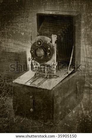 antique folding camera on grunge background - stock photo