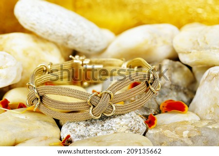 antique gold bracelet on stones with petals - stock photo