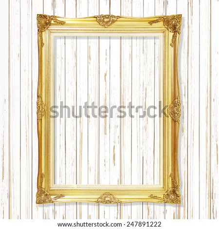 Antique gold frame on white wooden wall ;. Empty picture frame on white wooden wall. - stock photo
