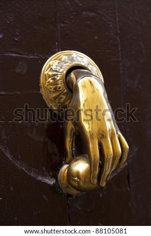 Antique Gold Hand Door-Knocker - stock photo