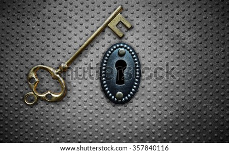 antique gold key and key hole on metal background                               - stock photo