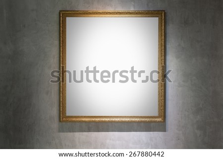 Antique golden frame on concrete wall in gallery  - stock photo