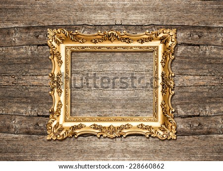 antique golden frame over rustic wooden background. grungy wallpaper - stock photo
