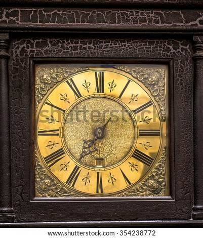 Antique grandfather clock face detail with distressed wooden casing.