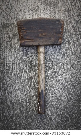 Antique hammer / mallet made of wood laying on a textured cement background. - stock photo