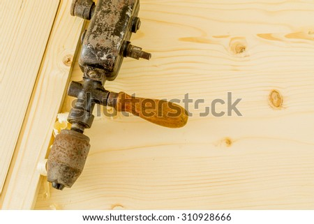 Antique hand drill on a wooden background