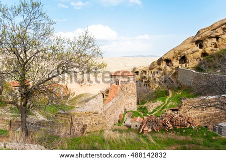 Antique historical David Gareji monastery complex built on cliff at Geargian-Azerbaijan border ridge. Colorful summertime vibrant outdoors horizontal image on blue cloudy sky background.