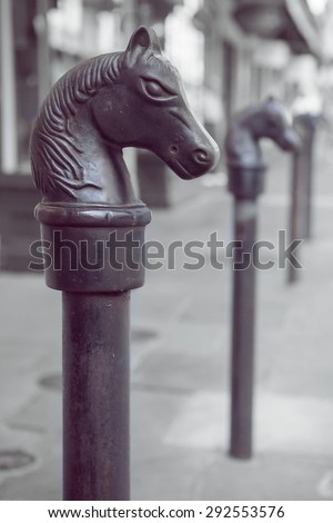 Antique horse head hitching post in the New Orleans French Quarter with shallow depth of field and retro filter effect - stock photo
