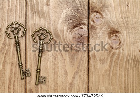 antique key on grunge wooden table - stock photo