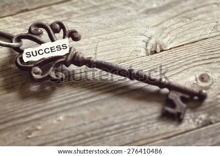 Antique key with word success written on paper resting on wooden surface concept for aspirations and success - stock photo