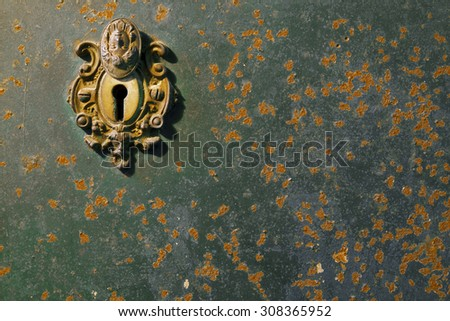 Antique keyhole on rusty metal surface with color paint flaking and cracking texture - stock photo