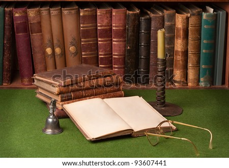Antique leather books, tin candlestick and reading glasses on green blotter. - stock photo